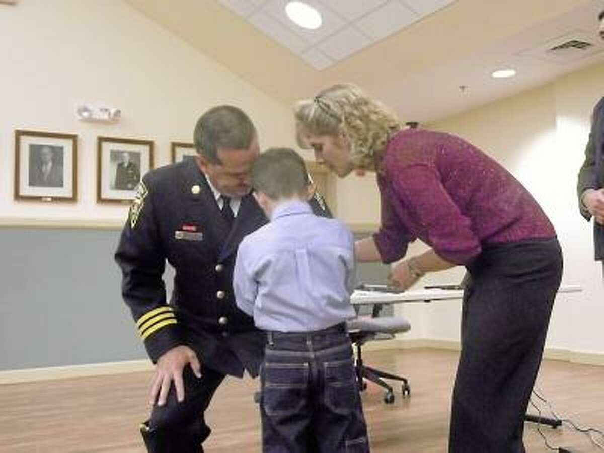 RICKY CAMPBELL/ Register Citizen New Torrington Fire Chief Gary Brunoli receives his pin from his 6-year-old grandson Elias on Wednesday night. Brunoli was voted on and sworn in as the new chief after a five-month process that included an intital 30 candidates.