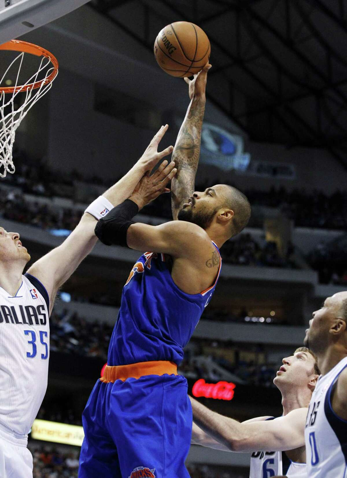 New York Knicks center Tyson Chandler takes a shot over Dallas Mavericks center Chris Kaman. Photo by The Associated Press