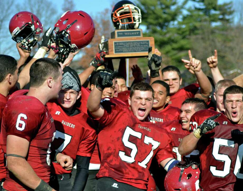 """Torrington's Tom Sommers (center) and his teammates celebrate with """"The Helmet"""" following their 35-13 victory over Watertown. Photo by Sean Meenaghan/Register Citizen"""