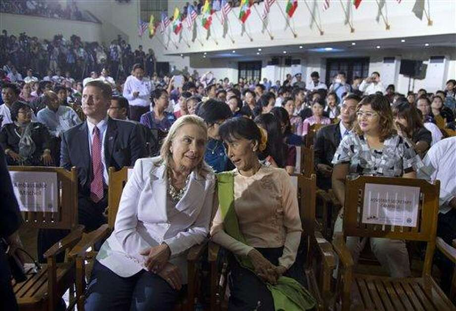 U.S. Secretary of State Hillary Rodham Clinton, left in foreground, and Myanmar opposition leader Aung San Suu Kyi sit together before U.S. President Barack Obama speaks at University of Yangon, in Yangon, Myanmar, Monday. The president dispatched Hillary from Southeast Asia to the Mideast, to try to calm the bloody conflict there.  (AP Photo/Carolyn Kaster) Photo: AP / AP