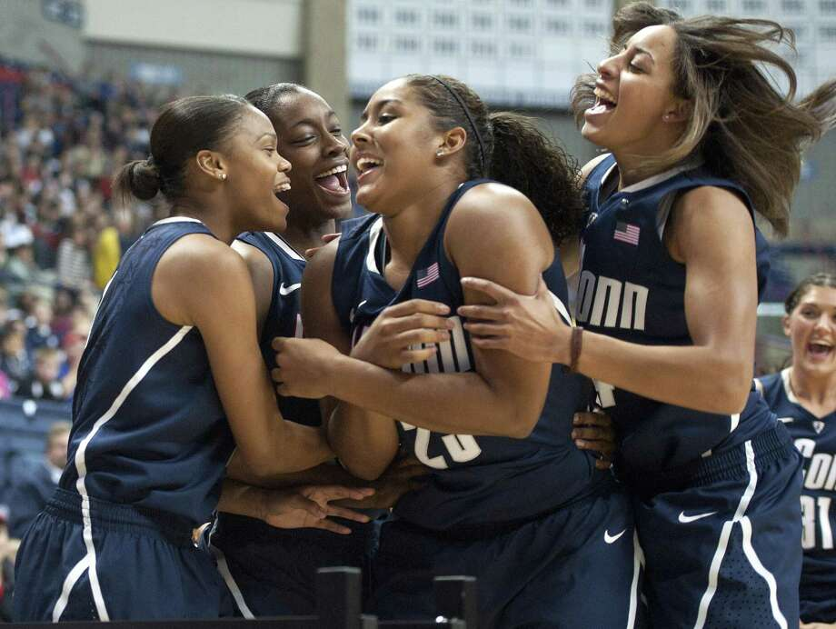 Connecticut's Kaleena Mosqueda-Lewis, second from right, is congratulated by teammates Moriah Jefferson, left, Brianna Banks, second from left, and Bria Hartley, right, after she won a 3-point competition among two men's players and two women's, at UConn's First Night event in Storrs, Conn., Friday, Oct. 12, 2012. By Associated Press Photo: ASSOCIATED PRESS / A2012
