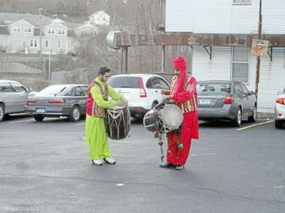 JASON SIEDZIK/ Register Citizen   Sheer Boota, left, and Mohammad Boota performed at the traditional prosperity ceremony for Winsted Grocery's grand opening.