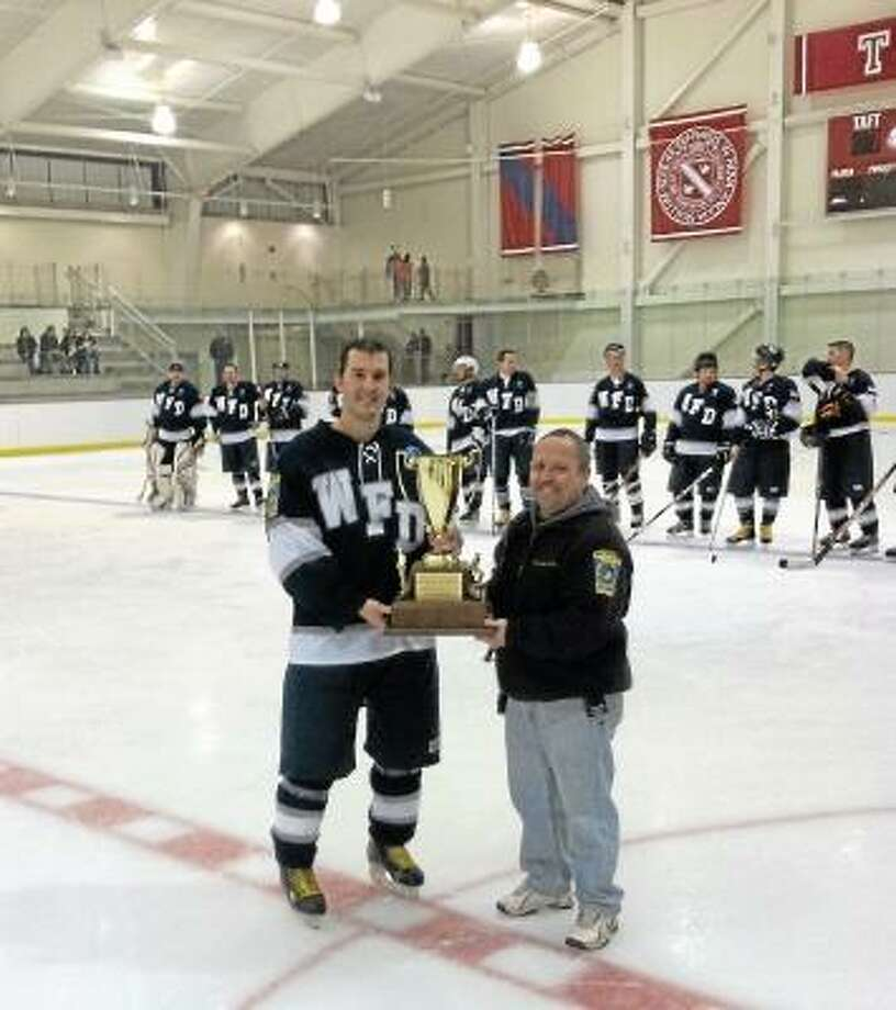 "Submitted photo Watertown Fire Department Hockey Team Co-Captain Brian White accepts the winners trophy as the Fire Department bested the Police Department, 7-1, in Saturday night's benefit ""Battle of the Badges"""