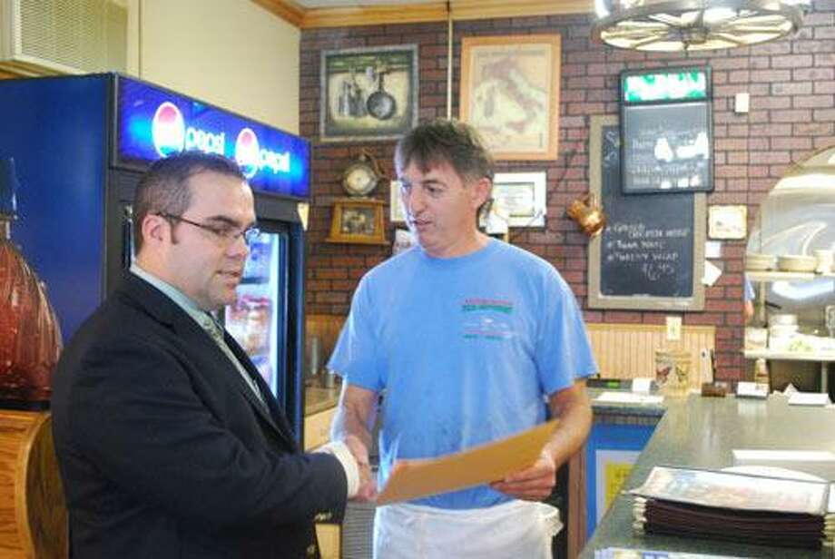 "Submitted Photo First Selectman Mike Criss shakes hands with Ilir ""Lucky"" Ziba, owner of Harwinton Pizza after Lucky received an official citation for his continued generosity and support of the town."