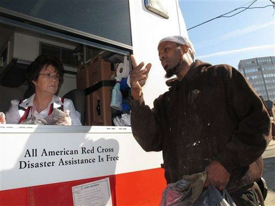 In this Nov. 12 photo, Red Cross volunteer Ellen Foreman, left, speaks with Ralph Royster, right, who was seeking a hot meal in Atlantic City, N.J., two weeks after Superstorm Sandy devastated the Jersey shore. Atlantic City is not in Bergen County, where problems, including a lack of hot food, have been reported.  (AP Photo/Wayne Parry) Photo: AP / AP