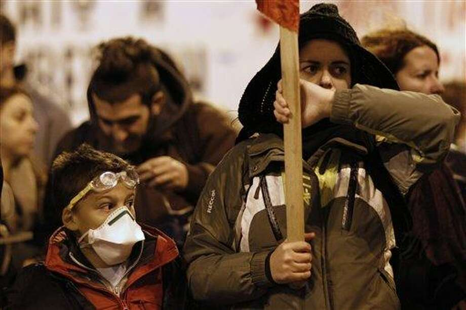 A child marches along with protesters during  a protest in Athens on Saturday, Nov. 17, 2012. Several thousand marchers are commemorating the 39th anniversary of a deadly student uprising against the then ruling dictatorship, with more than 6,000 police deployed in the center of the Greek capital. (AP Photo/Kostas Tsironis) Photo: AP / AP