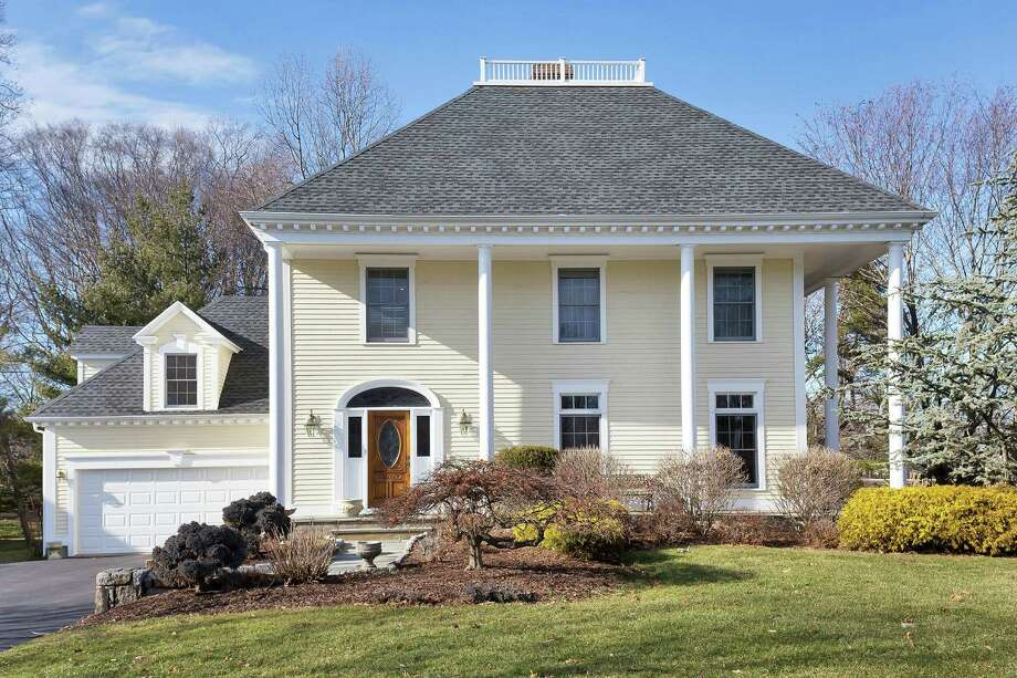 The colonial house at 10 Eagle Drive has a two-story covered and colonnaded wrap-around front porch.