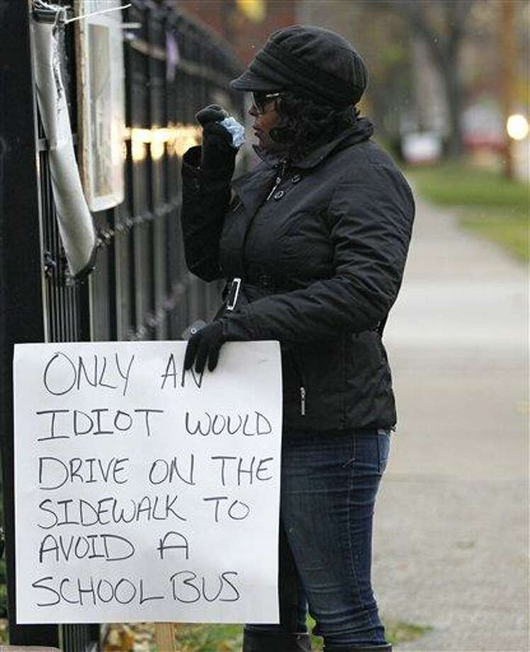 Shena Hardin wipes her nose as she holds up a sign to serve a highly public sentence Tuesday, Nov. 13, 2012, in Cleveland, for driving on a sidewalk to avoid a Cleveland school bus that was unloading children. A Cleveland Municipal Court judge ordered 32-year-old Hardin to serve the highly public sentence for one hour Tuesday and Wednesday. (AP Photo/Tony Dejak) Photo: AP / AP