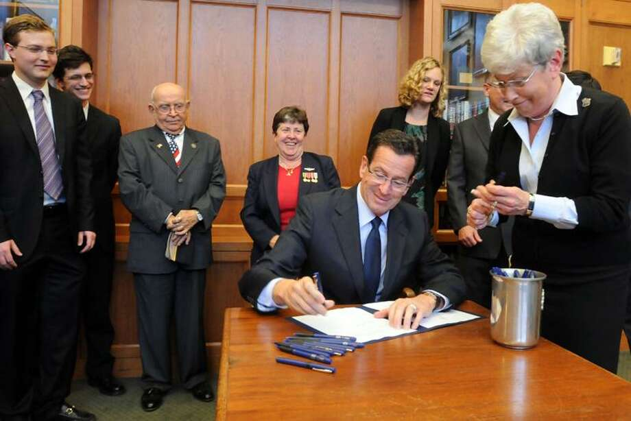 Four bills were recently passed by the CT legislature for new protections for CT veterans. Gov. Dannel Malloy (with Lt. Gov. Nancy Wyman's help) signed one in a ceremony at the Yale Law School where students in the school's Veterans Legal Services Clinic were key in calling attention to one of the bills. Left to right: Yale law students Jon Fougner and Eric Parrie, Rep. Al Adinolfi, Dept. of Veterans Affairs Commissioner Linda Schwartz, and Margaret Middleton, exec. dir. CT Veterans Legal Center. Mara Lavitt/New Haven Register11/12/12