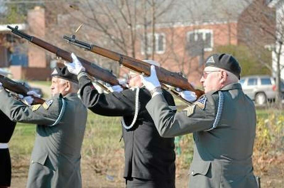 John Berry/Register Citizen      Torrington's Veterans Day ceremony, Sunday at Coe Memorial Park, included a rifle salute at 11 a.m. from veterans. Right to left,  Bud Atwood, Wayne Wilson and Rene Richards are among the veterans participating in the cremony.
