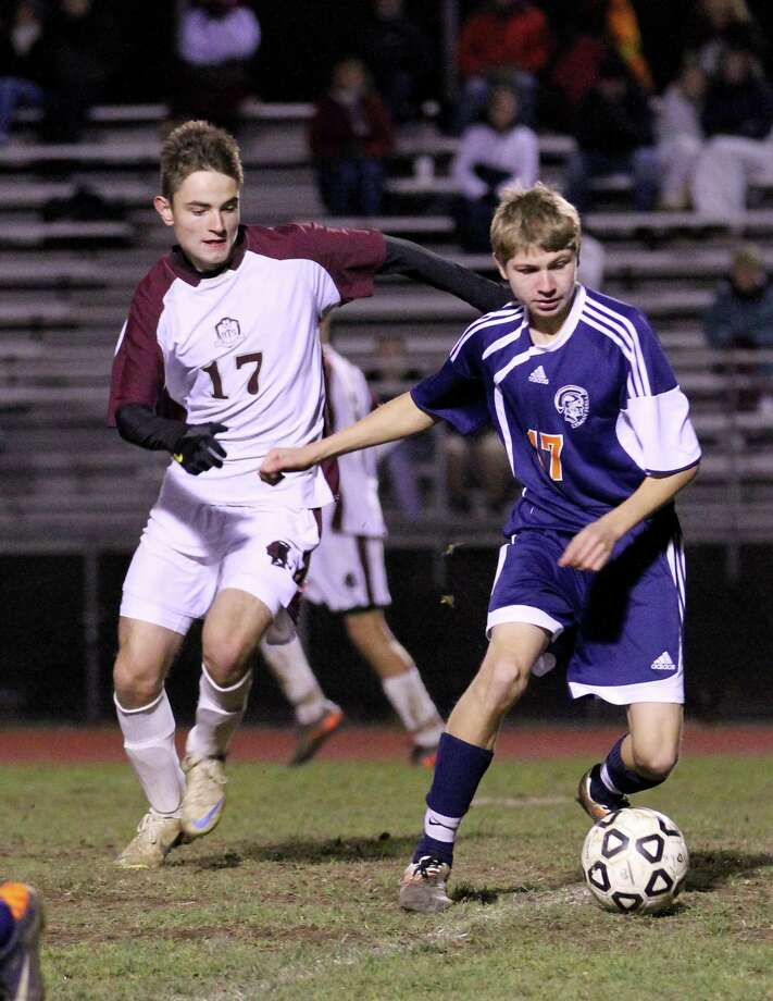 Alex Church (#14) of the Raiders controls the ball against Michael Grego (#7) of Lyman Hall Friday evening at the Robert H. Frost Sports Complex.  Photo by Marianne Killackey/Special to Register Citizen