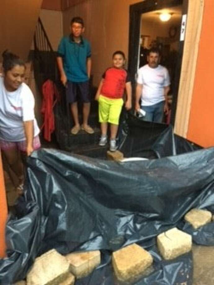 Francisco Pesina (right) and his family: (from right) sons Adrian, Miguel and wife, Marta, watch and brace for more rain. Their apartment in north Pasadena flooded their home, and more rain could mean having to move to find shelter. Photo: Y.c. Orozco