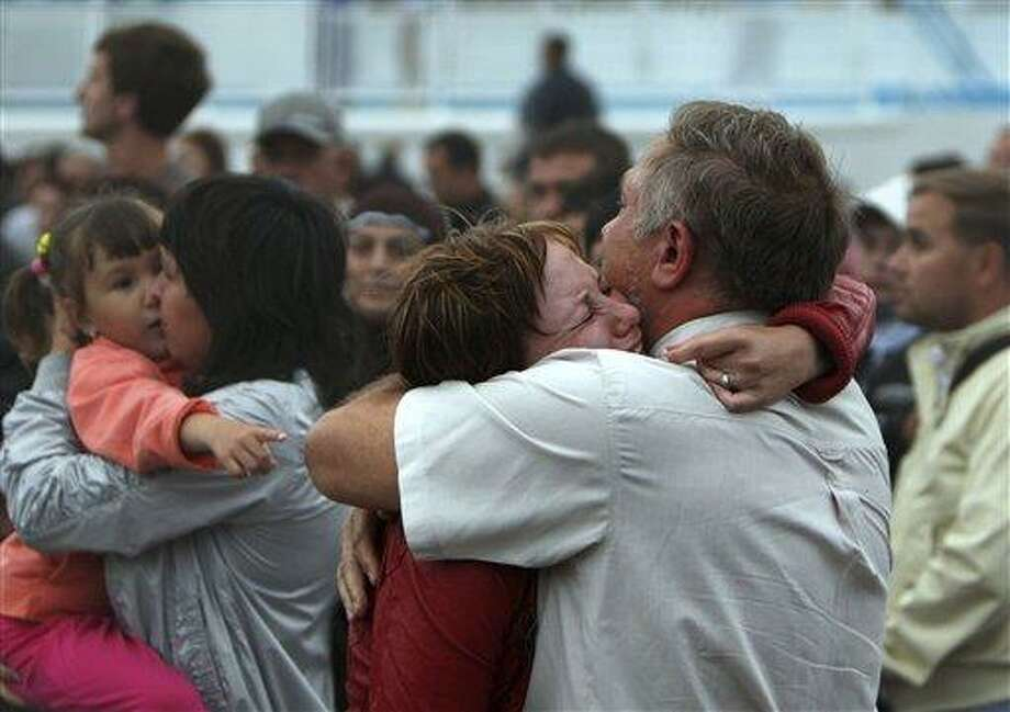 A relative embraces a survivor upon the arrival of the Arabella riverboat with dozens of survivors of a shipwreck in Kazan, on Sunday, July 10, 2011, on the Volga River, in central Russia. A woman drowned and some 100 remain missing after the double-decker passenger boat sank in the middle of the river some 3 kilometers (2 miles) away from the nearest bank, in the Tatarstan region, about 450 miles (750 kilometers) east of Moscow. (AP Photo/Roman Kruchinin) Photo: AP / AP