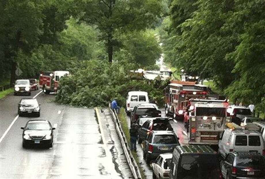 In this June 23, 2011 photo, rescue personnel work at the scene of a tree that fell onto the Merritt Parkway in Stamford, Conn., killing a Massachusetts man traveling along the roadway. Stately trees hugging the roadside are pretty but sometimes perilous, falling onto cars three times in recent weeks. (AP Photo/Stamford Advocate, Jack Nickerson) Photo: AP / Stamford Advocate File Photo