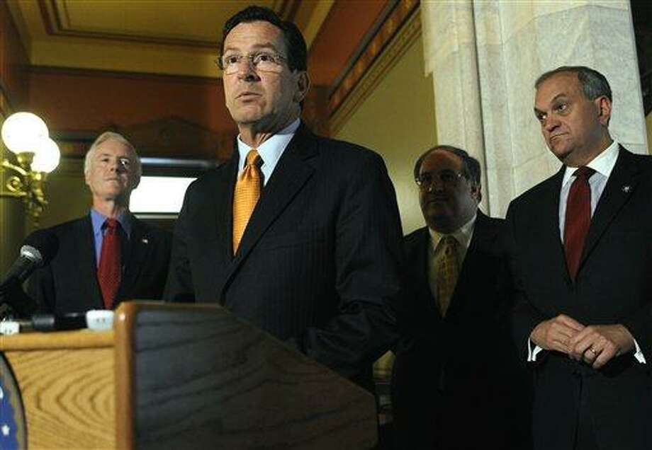 Connecticut Gov. Dannel P. Malloy, center, speaks to the media as Bridgeport Mayor Bill Finch, left, Waterbury Mayor Michael Jarjura, second from right, and New Haven Mayor John DeStafano, right, look on, at the Capitol in Hartford, Conn., Friday, June 24, 2011. A union vote on Friday scuttled a labor-concessions package that the governor was counting on to balance a two-year state budget, setting the stage for cuts that could include thousands of layoffs.  (AP Photo/Jessica Hill) Photo: AP / AP2011