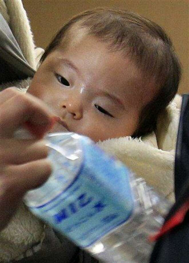 A baby looks at a bottled water as mother receives it at a ward office in Tokyo, Friday, March 25, 2011 as the Tokyo Metropolitan Government started on Thursday to distribute three small bottles of water each to an estimated 80,000 families with babies of 12 months or younger. (AP Photo/ Lee Jin-man) Photo: AP / AP
