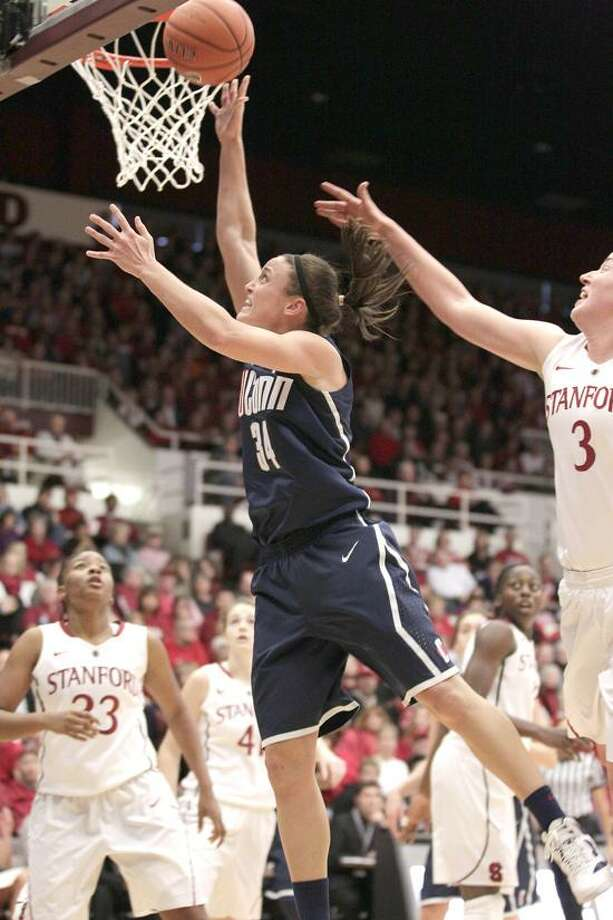 Connecticut guard Kelly Faris (34) drives to the basket against Stanford forward Mikaela Ruef (3) as guard Jasmine Camp (23) looks on during the first half of an NCAA college basketball game in Stanford, Calif., Saturday, Dec. 29, 2012. (AP Photo/Tony Avelar) Photo: AP / AP2012