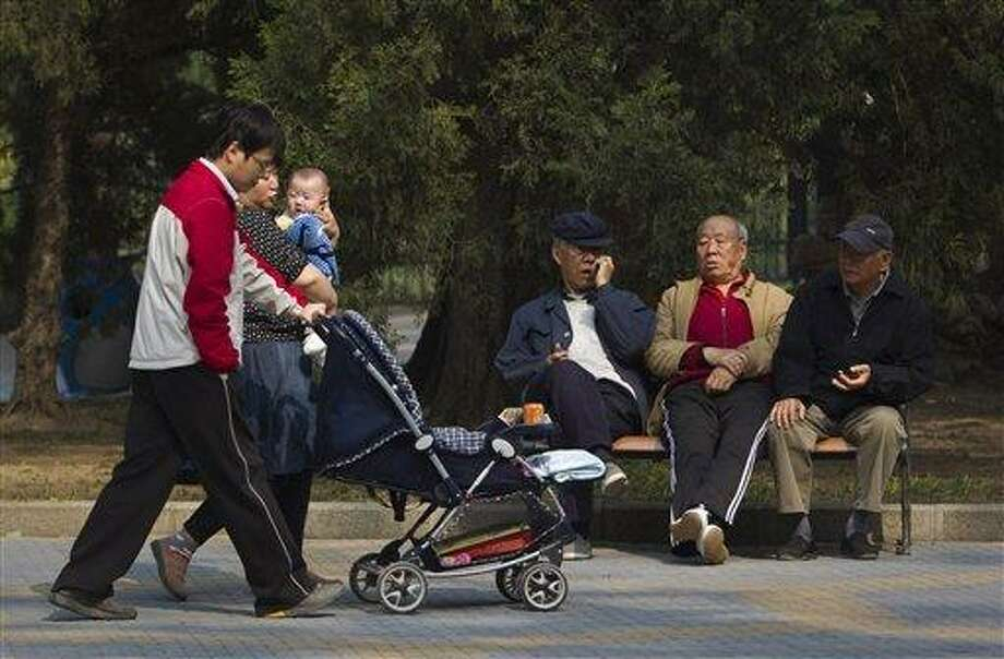 """Elderly men rest on a bench as a family with their new born baby walk past at a park in Beijing, China in 2011. China amended Friday its law on the elderly to require that adult children visit their aged parents """"often"""" - or risk being sued by them. Associated Press file photo Photo: AP / AP"""