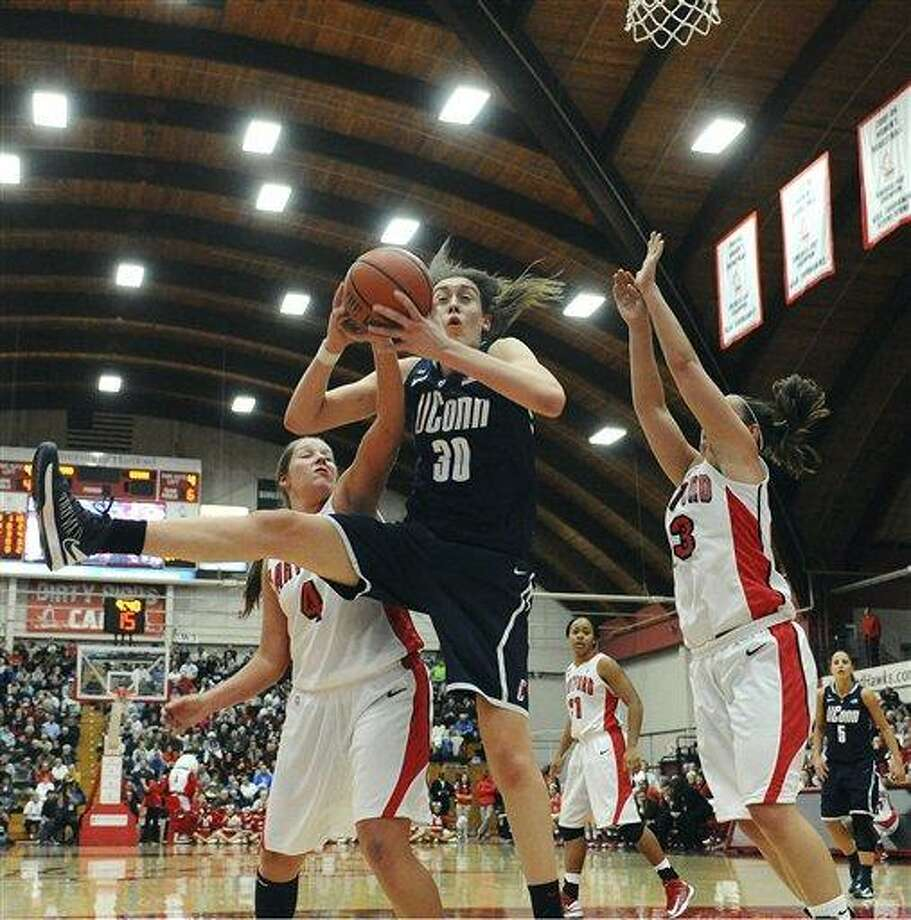 Connecticut's Breanna Stewart, center, snags a rebound while guarded by Hartford's Christie Michals, left, and Taylor Clark, right, during the second half of an NCAA women's college basketball game in West Hartford, Conn., Saturday, Dec. 22, 2012. Connecticut won 102-45. (AP Photo/Jessica Hill) Photo: ASSOCIATED PRESS / A2012