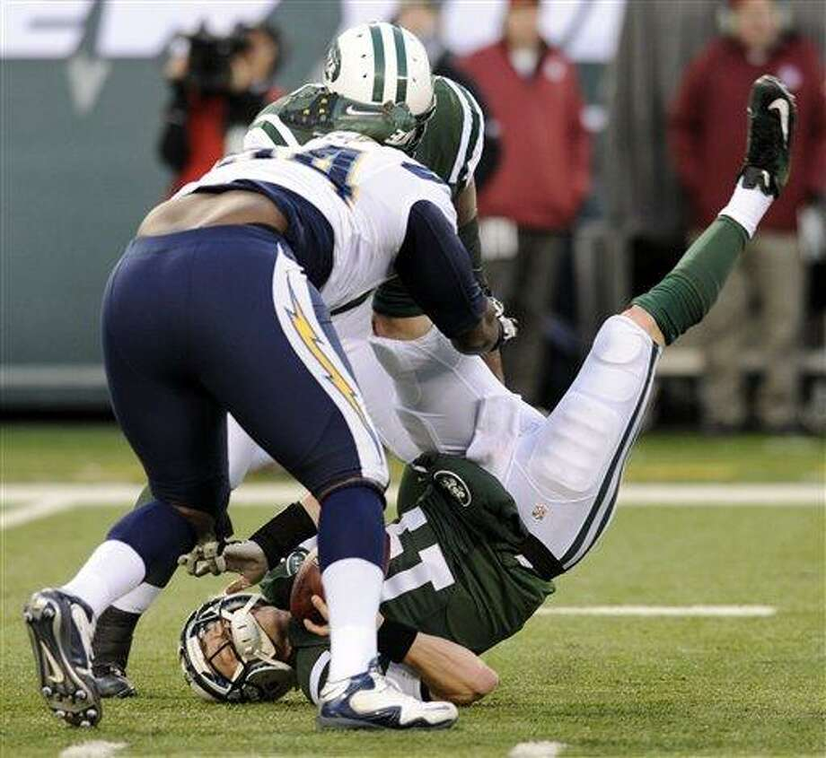 FILE - In this Dec. 23, 2012, file photo, New York Jets quarterback Greg McElroy, bottom, is sacked by San Diego Chargers defensive end Corey Liuget, front left, during the second half of an NFL football game in East Rutherford, N.J. McElroy, who was sacked 11 times last weekend, has a concussion and will be replaced by Mark Sanchez as the  Jets' starting quarterback in the season finale at Buffalo on Sunday, coach Rex Ryan said. (AP Photo/Bill Kostroun, File) Photo: ASSOCIATED PRESS / A2012