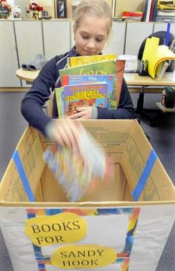Elizabeth Saddig age 11 of Naugatuck is collecting donated books to be given to children from the Sandy Hook School. The books are being collected at East Haven Public TV on Coe Ave. Mara Lavitt/New Haven Register  12/27/12