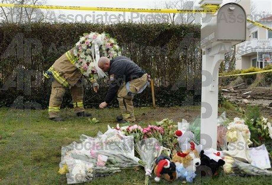 Firefighters adjust the position of a wreath that was part of a memorial at Stamford fire that claimed five lives on Christmas Day 2011. (AP)