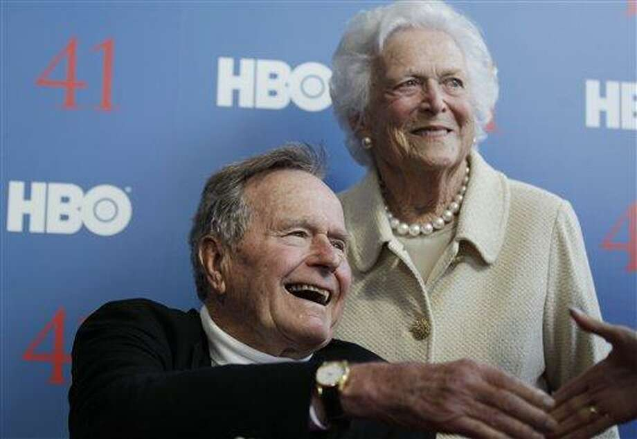 """FILE - In a Tuesday, June 12, 2012 file photo, former President George H.W. Bush, and his wife, former first lady Barbara Bush, arrive for the premiere of HBO's new documentary on his life near the family compound in Kennebunkport, Maine. Bush spokesman Jim McGrath said Wednesday, Dec. 26. 2012 that doctors at the Houston hospital where Bush has been treated for a month remain """"cautiously optimistic"""" that he will recover. Still, no discharge date has been set, and McGrath says that doctors are being cautious because at Bush's age """"sometimes issues crop up that are beyond anybody's ability to discern or foretell.""""(AP Photo/Charles Krupa, File) Photo: AP / AP"""