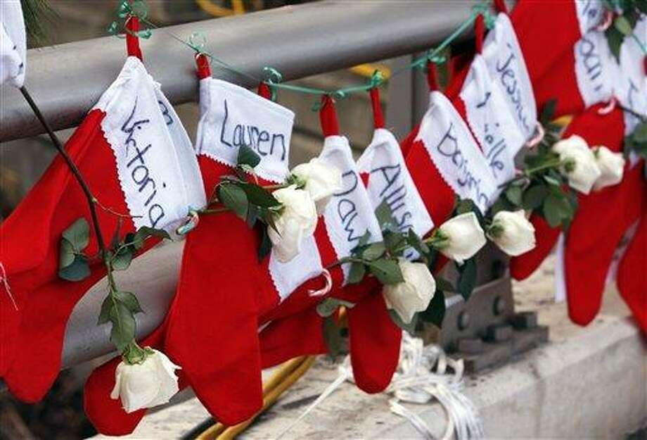 Christmas stockings with the names of shooting victims hang from railing near a makeshift memorial near the town Christmas tree in the Sandy Hook village of Newtown. In the wake of the shooting, the grieving town is trying to find meaning in Christmas. AP Photo/Julio Cortez Photo: AP / AP