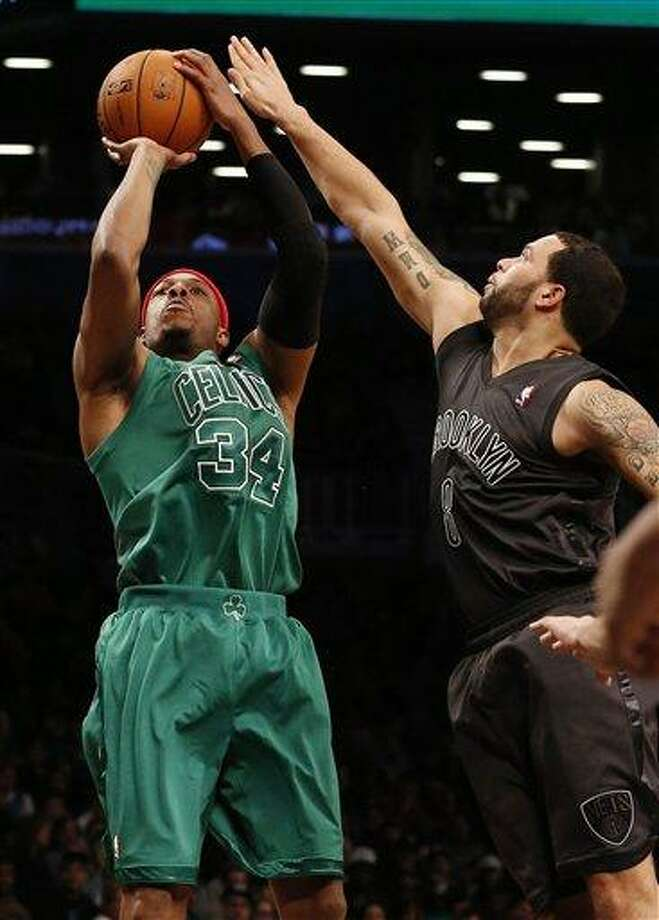 Boston Celtics forward Paul Pierce (34) shoots against Brooklyn Nets guard Deron Williams (8) in the second half of their NBA basketball game at Barclays Center, Tuesday, Dec. 25, 2012, in New York. Boston won 93-76. (AP Photo/John Minchillo) Photo: AP / FR170537 AP