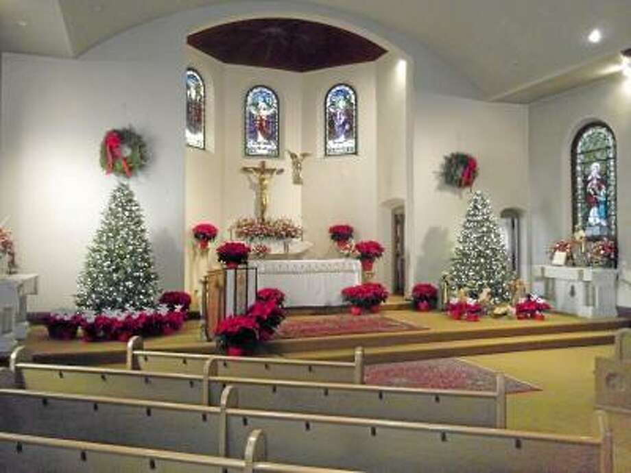 """St. Maron's Church in Torrington decorated its altar with poinsetta plants with the names of the 27 victims, who were killed in the Sandy Hook Elementary School shooting on Dec. 14, on angels as rememberance and part of the church's annual Christmas decorations. """"We have to remember that these beautiful victims are gifts,"""" said Father Larry Michael."""