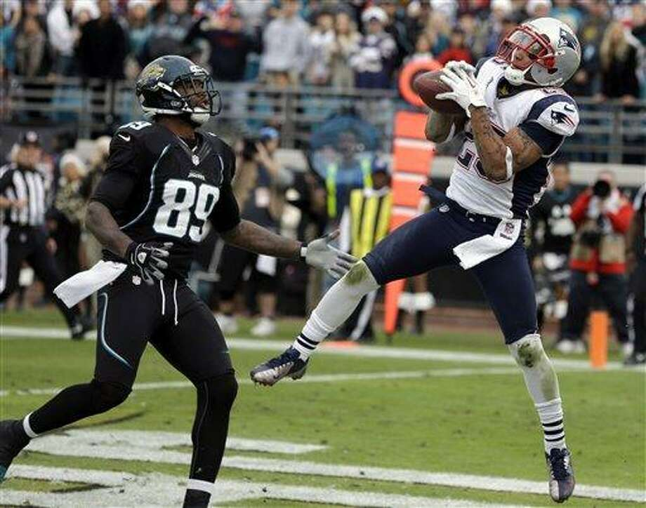 New England Patriots free safety Patrick Chung, right, intercepts a pass in front of Jacksonville Jaguars tight end Marcedes Lewis (89) as time expires in an NFL football game on Sunday, Dec.  23, 2012, in Jacksonville, Fla. New England won the game 23-16. (AP Photo/John Raoux) Photo: ASSOCIATED PRESS / AP2012
