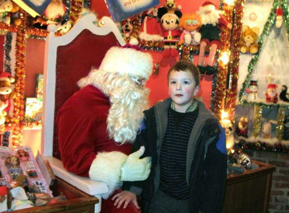 DEBBI MORELLO/ Register Citizen William Goodwin, 7, visited with Santa at Christmas Village on Sunday. This was the 64th year the magical village opened for children of all ages.