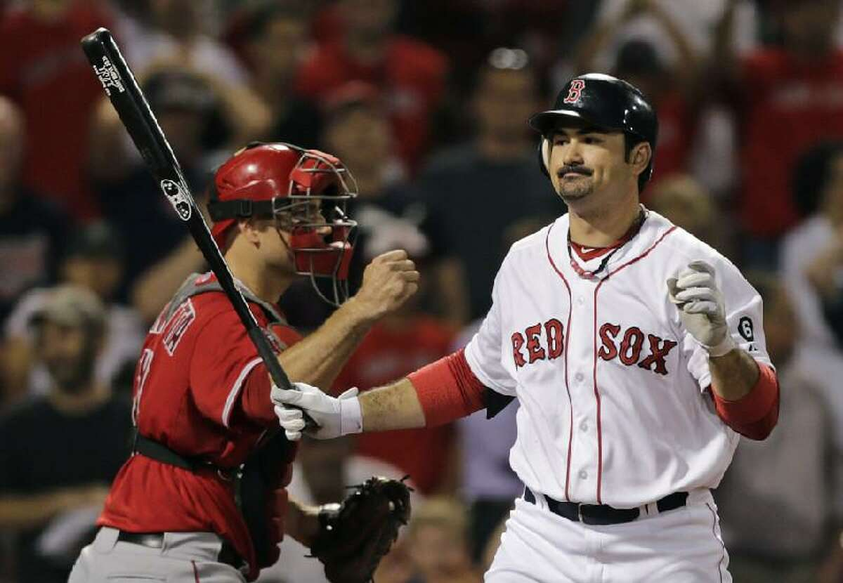 ASSOCIATED PRESS Boston Red Sox first baseman Adrian Gonzalez, right, reacts as he strikes out swinging to end the game as Los Angeles Angels catcher Chris Iannetta pumps Thursday night at Fenway Park in Boston. Gonzalez was scratched from the lineup Friday night as trade talks swirled between the Red Sox and Los Angeles Dodgers.