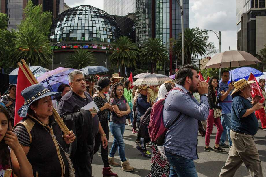 Demonstrators march past the Mexican Stock Exchange during a protest  against the North American Free Trade