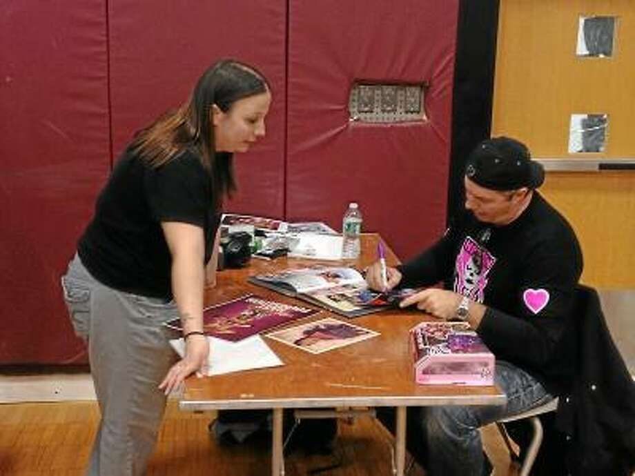 """RICKY CAMPBELL/ Register Citizen Bret Hart signs some wrestling memorabilia for Ludlow, Mass. resident Katie McCasland of KNS Collectibles. """"The Hitman"""" Hart was in Torrington for one night during Big Time Wrestling's three-stop tour deemed the 2012 Hart Attack Tour."""