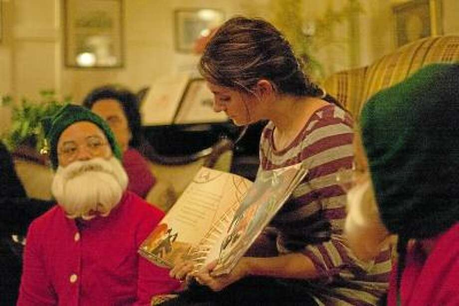 "Max Lauf/Register Citizen Jill Veras reads ""A Pirates Night Before Christmas"" during the toy shower at Yankee Pedlar Inn in Torrington. The event was a fundraiser for Christmas Village. / Max WIlliam Lauf"
