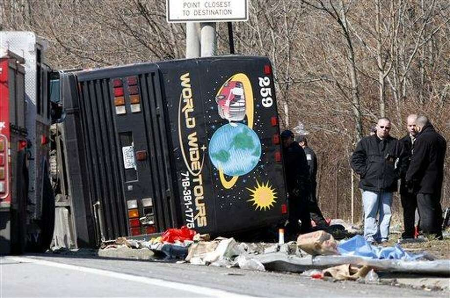 FILE--In this photo from Saturday, March 12, 2011, emergency personnel investigate the scene of a bus crash on Interstate-95 in the Bronx borough of New York. A verdict has been reached in a manslaughter case against the bus driver Ophadell Williams, charged in the crash that killed 15 passengers.  Williams has pleaded not guilty. He says a tractor-trailer cut him off and he lost control. The bus carrying gamblers coming from a Connecticut casino was sheared open like a sardine can when it struck a pole.  (AP Photo/David Karp, File) Photo: AP / FR50733 AP