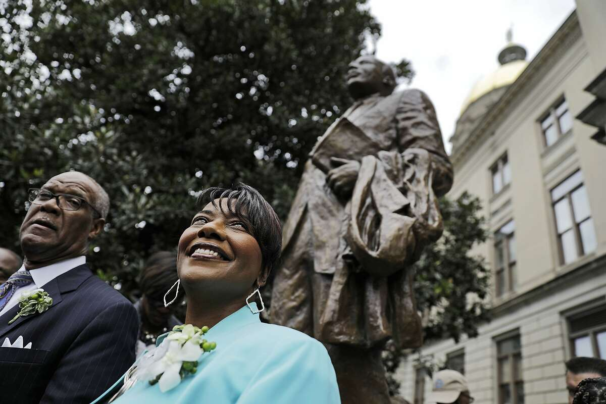 """The Rev. Bernice King, right, daughter of the Rev. Martin Luther King Jr., stands under a statue paying tribute to her father, after it's unveiled on the state Capitol grounds in Atlanta, Monday, Aug. 28, 2017. The statue's unveiling Monday came more than three years after Georgia lawmakers endorsed the project. A replica of the nation's Liberty Bell tolled three times before the 8-foot (2.44-meter) bronze statue was unveiled on the 54th anniversary of King's """"I have a dream"""" speech at the march on Washington. (AP Photo/David Goldman)"""