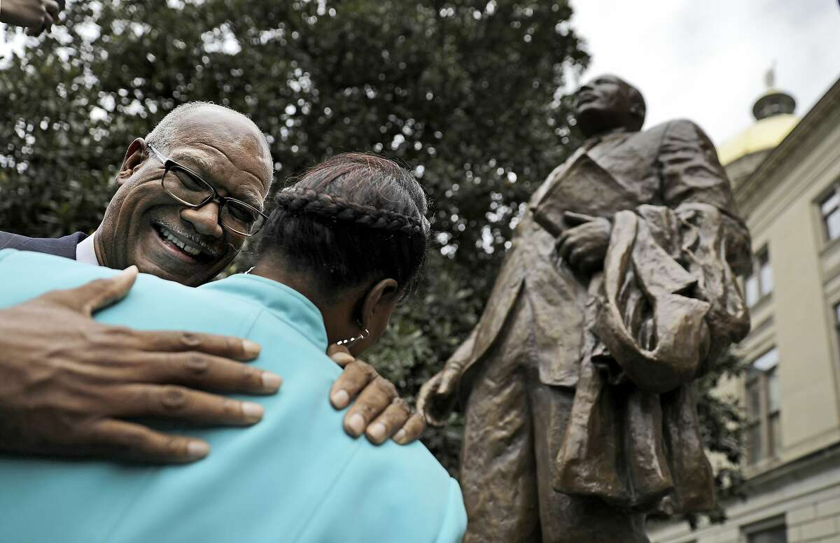 State Rep. Calvin Smyre, D - Columbus, left, embraces the Rev. Bernice King, daughter of the Rev. Martin Luther King Jr., after a statue paying tribute to her father, civil rights leader Martin Luther King Jr. is unveiled at the state Capitol in Atlanta, Monday, Aug. 28, 2017. Smyre, the longest-serving member of the House, sponsored the bill to place the statue on Capitol grounds. (AP Photo/David Goldman)
