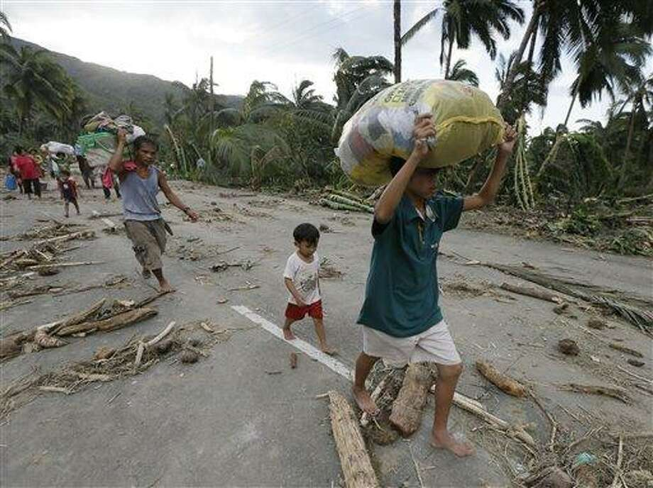 Residents walk to an evacuation center after retrieving their belongings at the flash flood-hit village of Andap, New Bataan township, Compostela Valley in southern Philippines, Wednesday Dec. 5, 2012.  Typhoon Bopha, one of the strongest typhoons to hit the Philippines this year, barreled across the country's south on Tuesday, killing scores of people while triggering landslides, flooding and cutting off power in two entire provinces. (AP Photo/Bullit Marquez) Photo: AP / STF