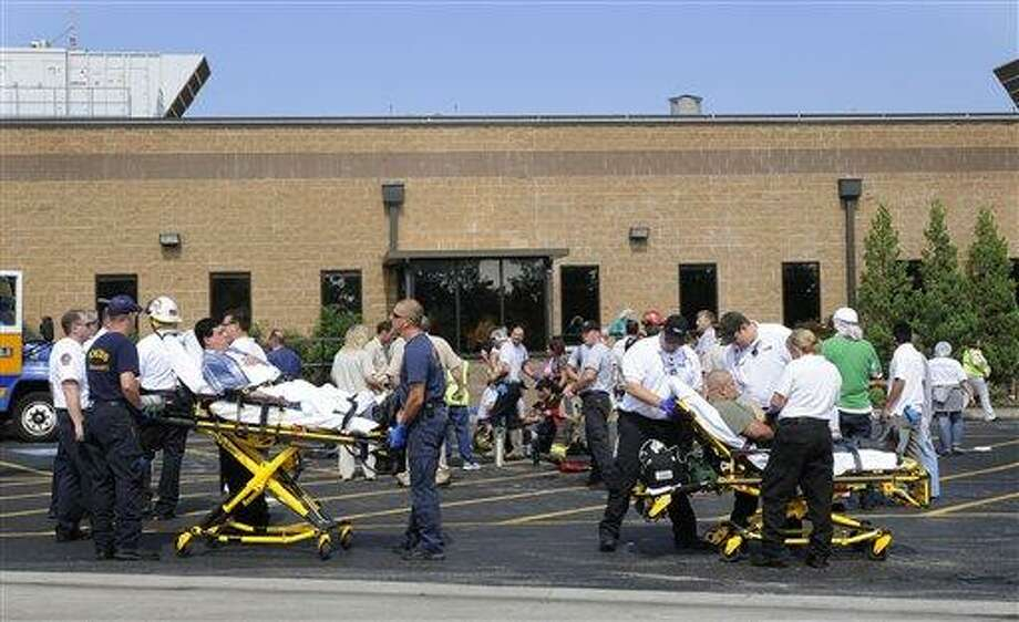 File - In a June 27, 2011 file photo, employees at the Tyson food processing plant in Springdale Ark., are helped by emergency personnel after being exposed to chlorine gas. The chlorine gas leak that sickened nearly 200 people  happened because a worker who couldn't read the English-language label on a barrel of chemicals inadvertently poured bleach into it, the Centers for Disease Control and Prevention said in a report released Thursday.(AP Photo/The Morning News, Spencer Tirey, File) Photo: AP / The Morning News