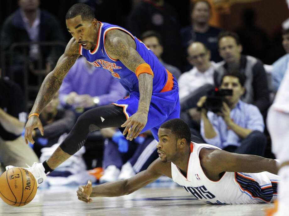 New York Knicks' J.R. Smith, top, and Charlotte Bobcats' Michael Kidd-Gilchrist, bottom, chase a loose ball during the second half of an NBA basketball game in Charlotte, N.C., Wednesday, Dec. 5, 2012. The Knicks won 100-98. (AP Photo/Chuck Burton) Photo: ASSOCIATED PRESS / AP2012