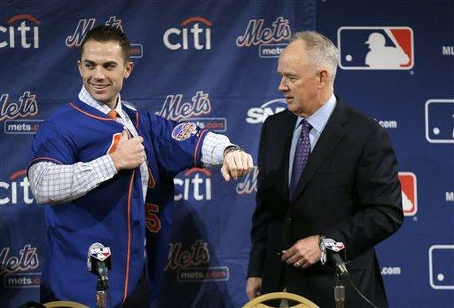 New York Mets third baseman David Wright puts on a Mets jersery as general manager Sandy Alderson looks on at right during a news conference at the baseball winter meetings on Wednesday, Dec. 5, 2012, in Nashville, Tenn. Wright has signed a contract extension with the New York Mets through 2020. (AP Photo/Mark Humphrey) Photo: ASSOCIATED PRESS / AP2012
