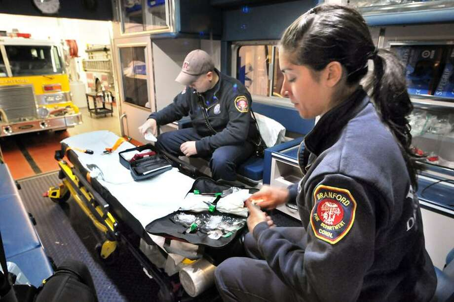 At Branford fire department headquarters, Branford Firefighters/Paramedics Amanda Mark and Jeff O'Connor work through a truck check on the department's ambulance. The check makes sure that all supplies are current and on board.  Mara Lavitt/New Haven Register  12/1/12