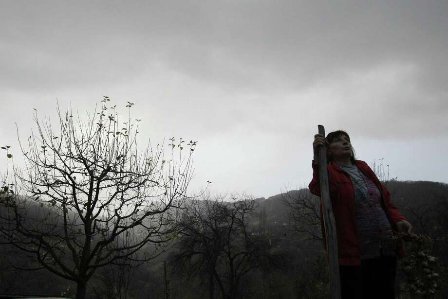 In this Nov. 30 photo Milka Prokic is seen at twilight with a garland of garlic and a wooden stake, in the village of Zarozje, near the Serbian town of Bajina Basta. Get your garlic, wooden crosses and stakes ready: a bloodsucking vampire is on the loose.  Or so say villagers in the tiny western Serbian hamlet of Zarozje, nestled between the lush green mountain slopes and spooky thick forests. Rumors that a legendary vampire ghost has returned are spreading panic throughout the town. An official warning telling villagers to put garlic in their pockets and place wooden crosses in each of their rooms, the tools that should keep away the vampires  did nothing but fuel the fear.  ASSOCIATED PRESS PHOTO/Darko Vojinovic Photo: ASSOCIATED PRESS / AP2012