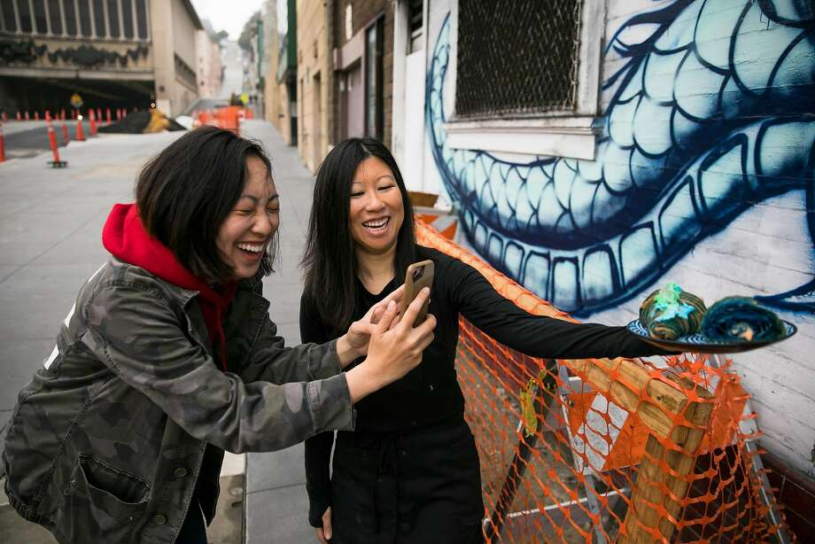 Amanda Sage (left) laughs as she takes a picture of her Blue Beard Dragon bicolor croissant with the help of Enter the Cafe owner Jessica Moy in S.F. The Blue Dragon mural outside of Enter the Cafe inspired Baker Doe to create the Blue Beard Dragon croissant. Photo: Mason Trinca, Special To The Chronicle