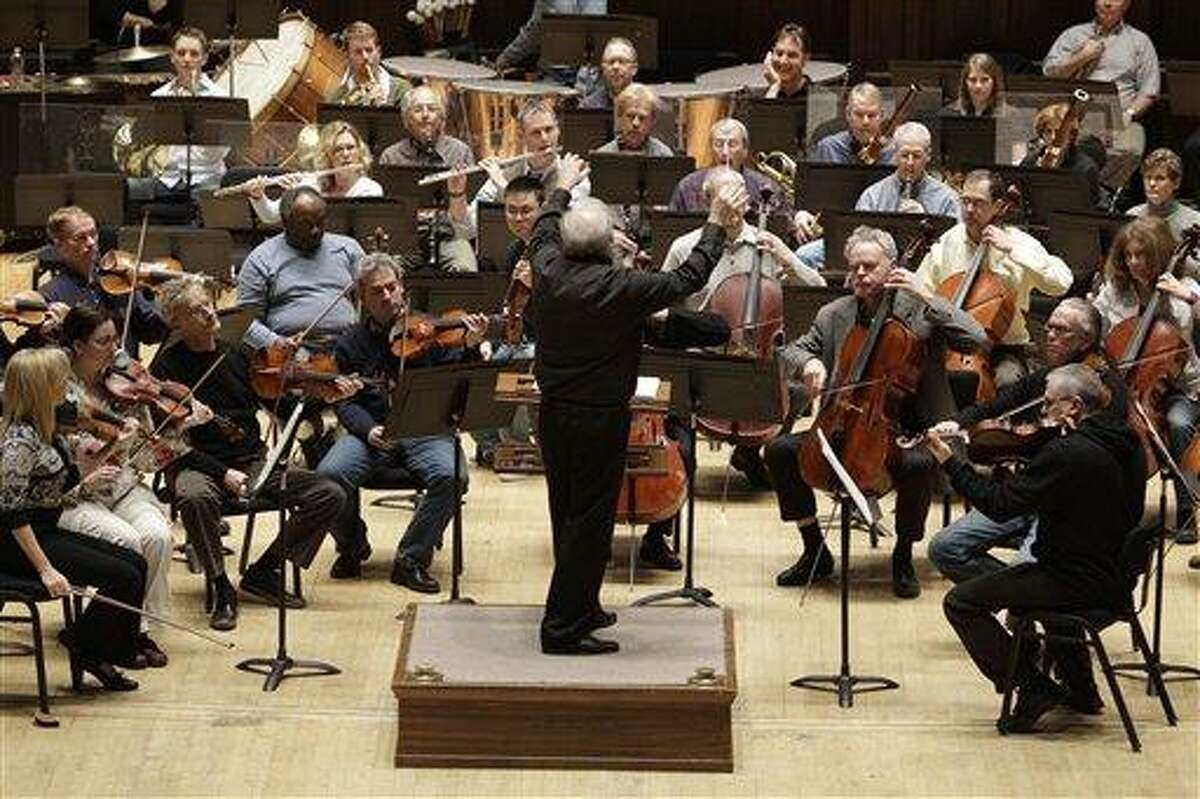 """Detroit Symphony Orchestra Musical Director Leonard Slatkin leads the orchestra during a rehearsal in Detroit, Thursday, April 7, 2011. Slatkin says the most difficult thing about the six-month musicians' strike for him was """"standing by and not doing anything."""" (AP Photo/Carlos Osorio)"""