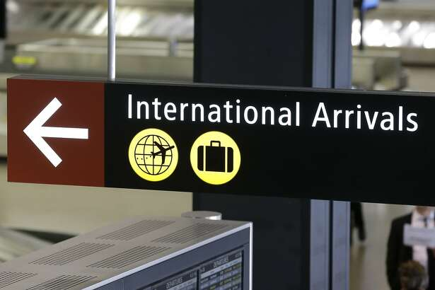 """A sign for International Arrivals is shown at the Seattle-Tacoma International Airport, Monday, June 26, 2017, in Seattle. The Supreme Court said Monday that President Donald Trump's travel ban on visitors from Iran, Libya, Somalia, Sudan, Syria and Yemen can be enforced if those visitors lack a """"credible claim of a bona fide relationship with a person or entity in the United States,"""" and that justices will hear full arguments in October, 2017. (AP Photo/Ted S. Warren)"""