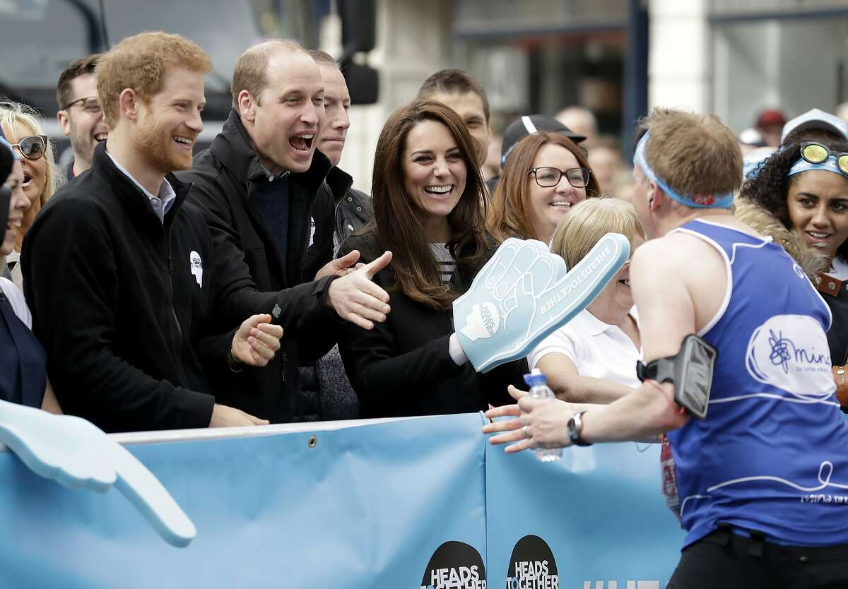 In this file photo dated Sunday, April 23, 2017, Britain's Prince William, his wife Kate and brother Prince Harry, left, as they encourage runners at a Heads Together cheering point along the route of the 2017 London Marathon in London. Heads Together is a mental health charity supported by the three British royals. Princess Diana died 20-years ago after a car accident Sunday, Aug. 31, 1997, in Paris, and the legacy left by her seems to live on through her two sons, who have passionately adopted their mother's more personal approach to the monarchy and to the public. (AP Photo/Matt Dunham, File)