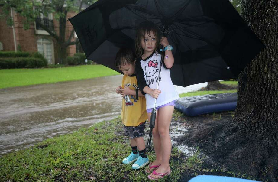 Two children use an umbrella while staying off flooded streets as people were evacuated from their homes near Crossroads and Walkwood drives during Tropical Storm Harvey Monday, Aug. 28, 2017, in Houston. Photo: Godofredo A. Vasquez, Houston Chronicle / Godofredo A. Vasquez